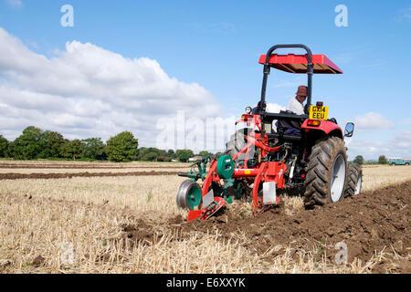 eine moderne rote 2014 Traktor mit Pflug, während in einem Landwirtschaft pflügen Match in der Landschaft von West - Stockfoto