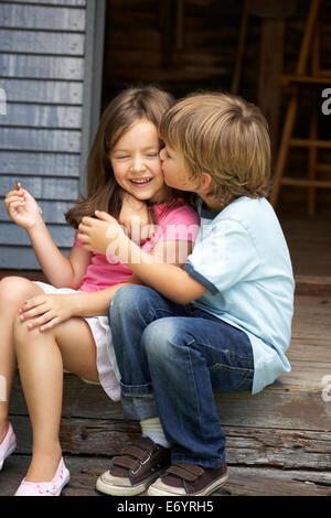 Junge Schwester auf Veranda zu küssen - Stockfoto