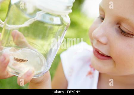 Kleines Mädchen mit Cricket in einem Glas - Stockfoto