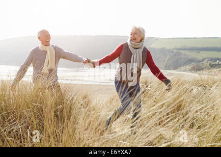 Älteres paar Wandern durch Sanddünen am Winter-Strand - Stockfoto
