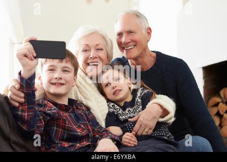 Großeltern und Enkelkinder auf Sofa nehmen Selfie - Stockfoto