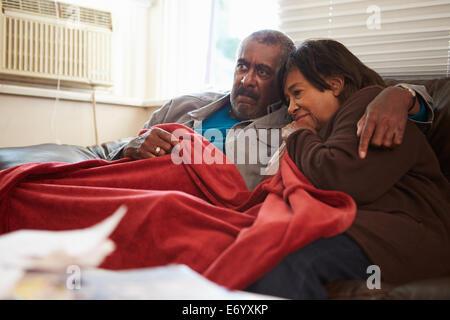 Älteres Paar versucht zu halten Warm unter der Decke zu Hause - Stockfoto
