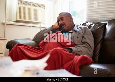 Ältere Mann versucht zu Hause unter Decke Warm zu halten - Stockfoto