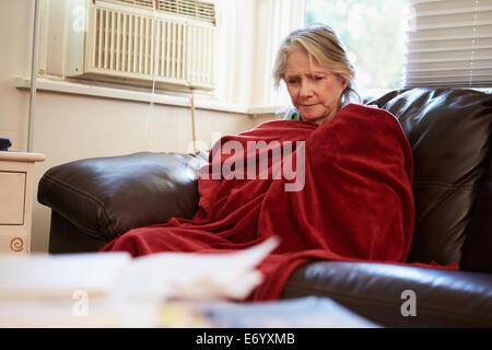 Ältere Frau, die versucht, zu Hause Warm unter der Decke zu halten - Stockfoto