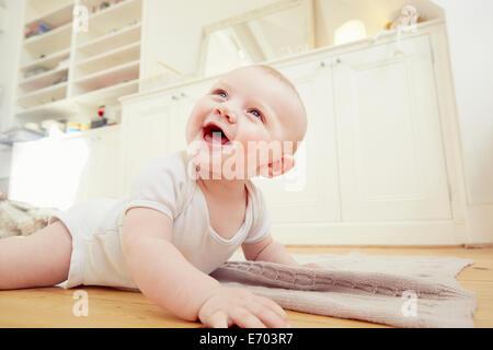 Lächelnden jungen auf Wohnzimmer Boden kriechen - Stockfoto