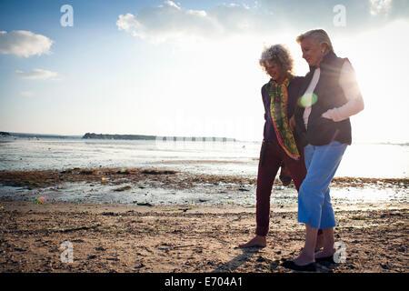 Mutter und Tochter zu Fuß am Strand