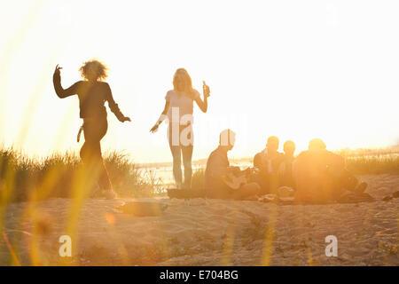 Sechs Erwachsene Freunde feiern bei Sonnenuntergang am Strand von Bournemouth, Dorset, Großbritannien