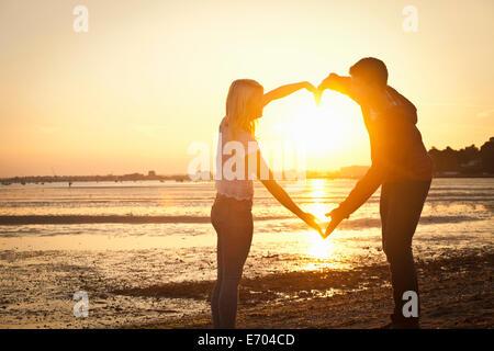 Paar bilden Herzform mit Armen am Strand bei Sonnenuntergang - Stockfoto