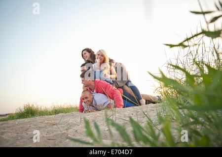 Gruppe von Freunden machen menschliche Haufen am Strand - Stockfoto