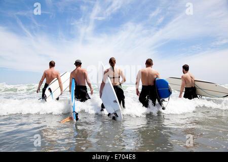 Rückansicht einer Gruppe von männlichen und weiblichen Surfer Freunde waten in Meer mit Surfbrettern