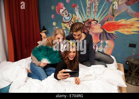 Drei Erwachsene Freunde auf Hotelbett nehmen Selfie auf smartphone - Stockfoto