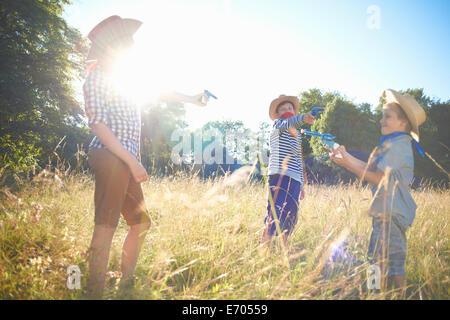 Drei junge Burschen, die verkleidet als Cowboys, Spielzeugpistolen holding