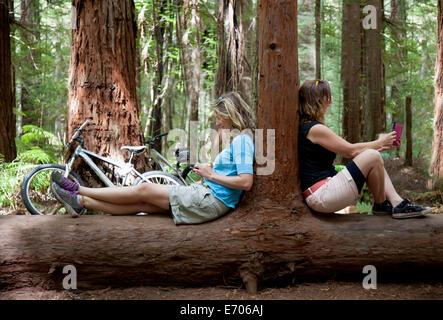 Zwei Frauen blickte auf Smartphone und Tablet-digital im Wald - Stockfoto