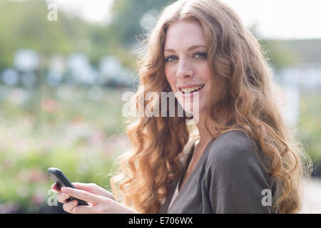 Porträt der jungen Frau SMS auf Smartphone im Garten - Stockfoto