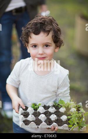 Porträt eines jungen hält Eierkarton und Pflanzen im Garten - Stockfoto