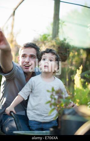 Mitte erwachsener Mann und Sohn suchen überrascht im Garten - Stockfoto