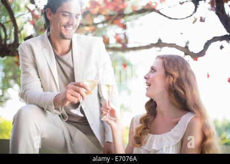 Paar, toasten gegenseitig mit Champagner im Gartenrestaurant - Stockfoto