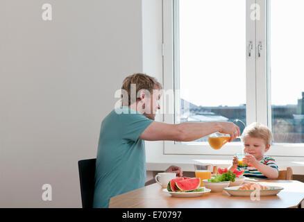 Sohn von Vater und Kind frühstücken am Küchentisch