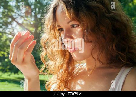 Porträt der jungen Frau blickte auf etwas in der hand glühend - Stockfoto