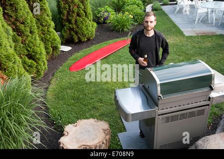 Porträt von Mitte erwachsenen Mann, der vom Grill mit Flasche Bier im Garten - Stockfoto