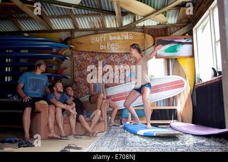 Fünf junge Erwachsene Surfer-Freunde in Surf Schuppen herumalbern - Stockfoto