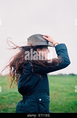 Eine Frau mit langen Haaren im Wind geblasen mit ihrem Hut. - Stockfoto