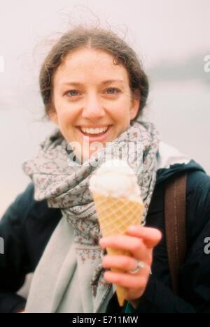 Eine Frau hält sich ein Eis in einem Kegel und lachen. - Stockfoto