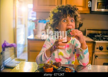 Porträt von überrascht Mädchen essen Muffins am Küchentisch - Stockfoto