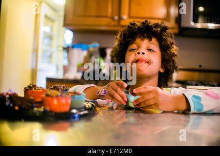 Porträt eines Mädchens mit Schokolade bedeckt Mund Essen Muffins - Stockfoto