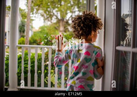 Rückansicht des Mädchens Schiebetür offene Terrasse - Stockfoto