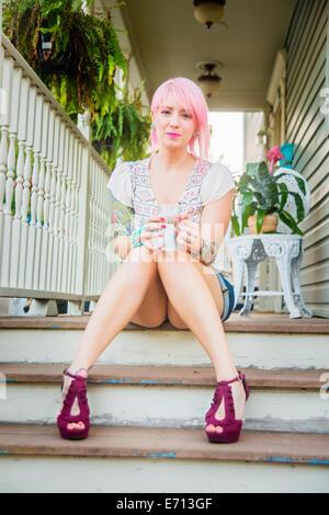 Porträt der jungen Frau mit rosa Haaren sitzen auf der Veranda Schritte Stockfoto