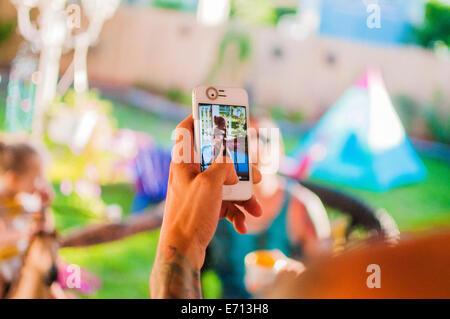 Mitte erwachsener Mann Fotografieren Freunde auf Smartphone im Garten - Stockfoto