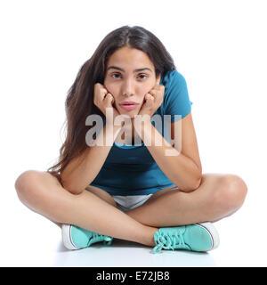 Gelangweilter Teenager Mädchen sitzen mit gekreuzten Beinen auf einem weißen Hintergrund isoliert - Stockfoto