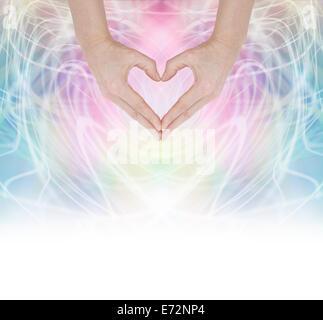 Hände, die Form eines Herzens auf einer wirbelnden Pastell Regenbogen Energie Hintergrund verblassen in weiß an - Stockfoto