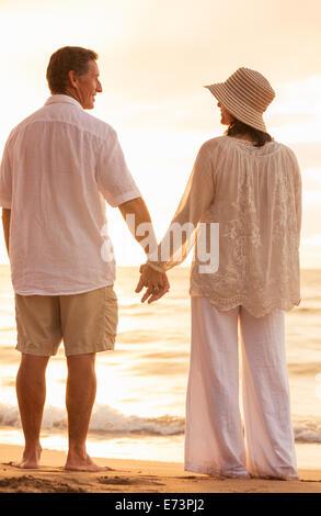 Romantische älteres paar Hand in Hand bei Sonnenuntergang am Strand genießen - Stockfoto