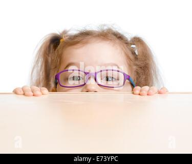 Lustiges Mädchen in Brillen versteckt sich hinter einem Tisch - Stockfoto