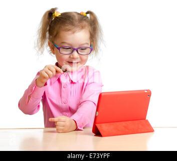 glückliches Kind in Gläsern Blick auf Mini-Tablet-pc-Bildschirm sitzen am Tisch - Stockfoto