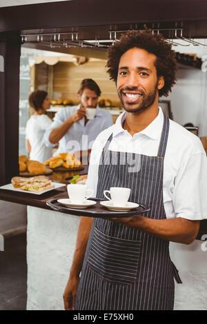 Hübscher Kellner lächelnd in die Kamera hält Tablett - Stockfoto