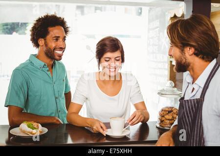 Barista mit zwei Kunden sprechen - Stockfoto