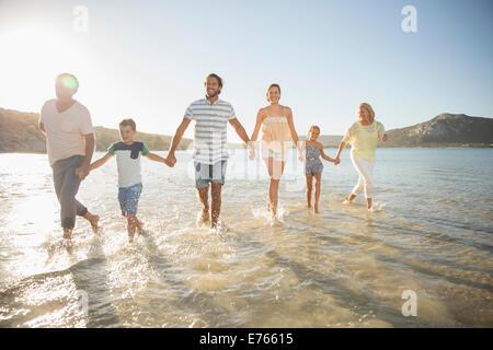 Familie gehen im seichten Wasser am Strand - Stockfoto