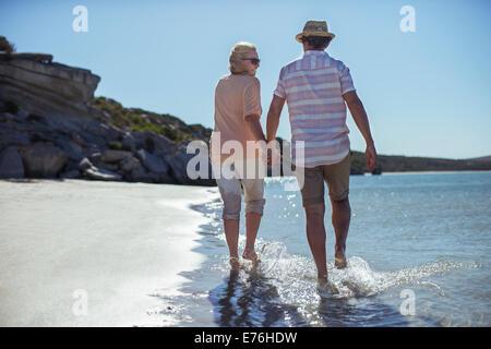 Paar Hand in Hand zu Fuß entlang der Küste - Stockfoto