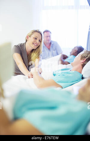 Frau im Gespräch mit Freund im Krankenzimmer - Stockfoto