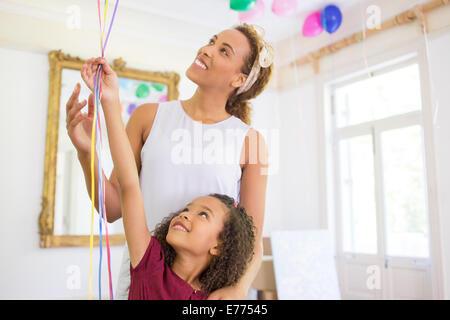 Mutter und Tochter Ballons zusammenhalten - Stockfoto