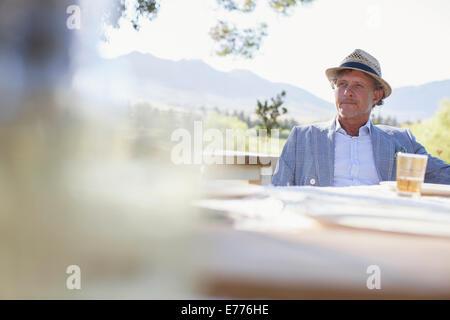 Älterer Mann sitzt am Esstisch im freien - Stockfoto