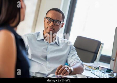 Ein Mann und eine Frau im Gespräch in einem Büro. - Stockfoto