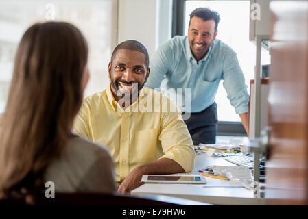 Drei Menschen in einem Büro, zwei Männer und eine Frau mit Computer-Monitor und digital-Tablette. - Stockfoto