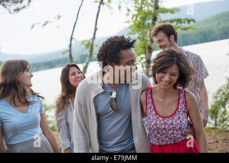 Eine Gruppe von Menschen, die genießen eines gemütlichen Spaziergang an einem See. - Stockfoto