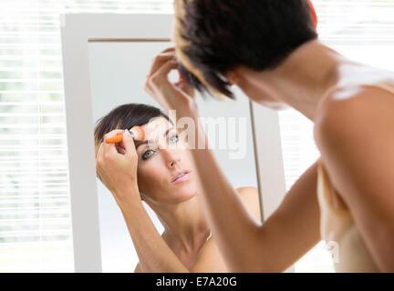 junge Frau beim Rouge Schminken mit Pinsel in Spiegel - Stockfoto