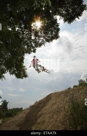 Ein BMX-Fahrer in der Luft an der Spitze des Abhanges Schlamm - Stockfoto