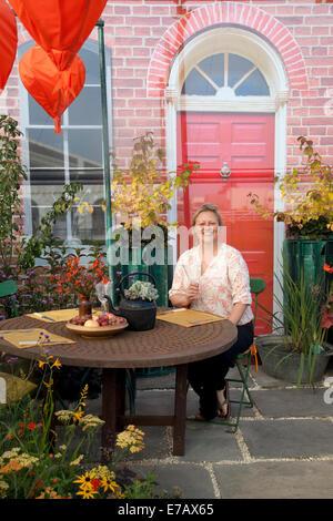 Frau saß im Garten im Innenhof in Harrogate, Yorkshire, UK. 11. September 2014. Lisa Watson mit 'findige' - Grundlagen - Stockfoto